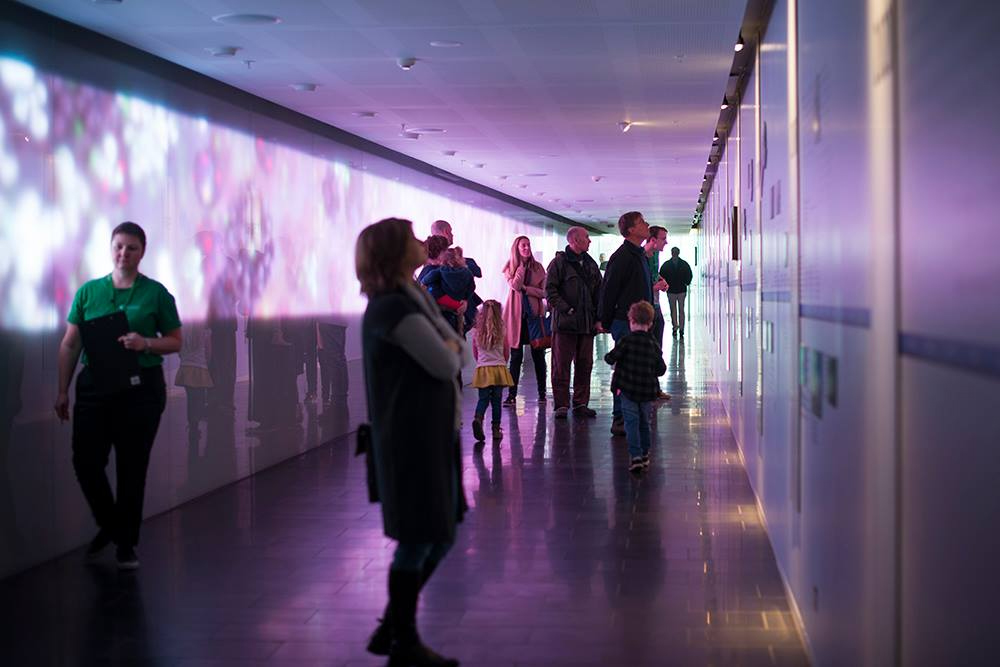 people standing in a hallway lit up with purple lights