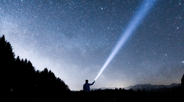 a person standing in front of a starry sky holding a flashlight