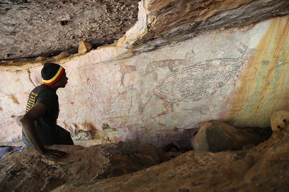 a man sits in a cave looking up at a painting of a kangaroo